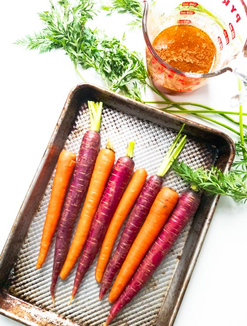Roasted rainbow carrots are the perfect winter to spring vegetable side dish. We love this lemon sesame (tahini) dressing drizzled on top. Easy one pan dish. Gluten free, dairy free, paleo, Whole30 and wahls protocol compliant. Peelwithzeal.com