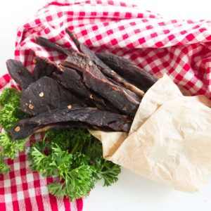 chili lime beef jerky wrapped in paper on a plaid napkin