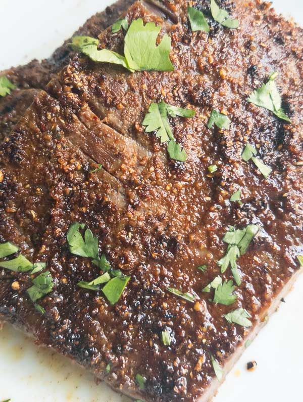 Spice Crusted Grilled Flank Steak (or skirt steak). Easy and quick to make for a weeknight dinner, leftovers for an awesome lunch. Gluten, dairy and allergy free dinner recipe. Simple spice rub with a unique twist. #grilling #recipes #steak #flanksteak #gluten free
