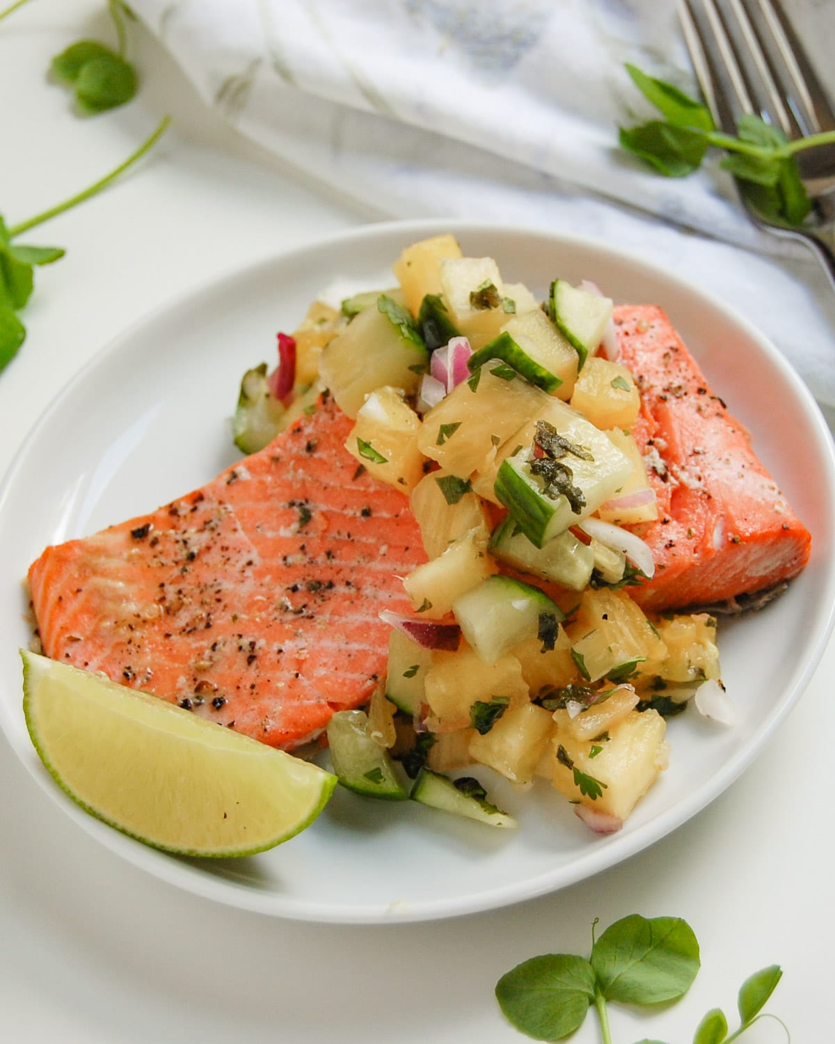 roasted salmon filet with pineapple salsa on white plate