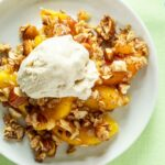close up of peach crisp on a plate with ice cream