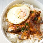 egg, sardines in tomato sauce on rice in white bowl
