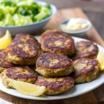 brown and crispy fish cakes on white plate with lemon wedges