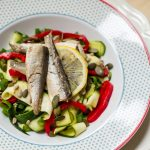 sardines on zucchini ribbons and red peppers with lemon in patterned white bowl