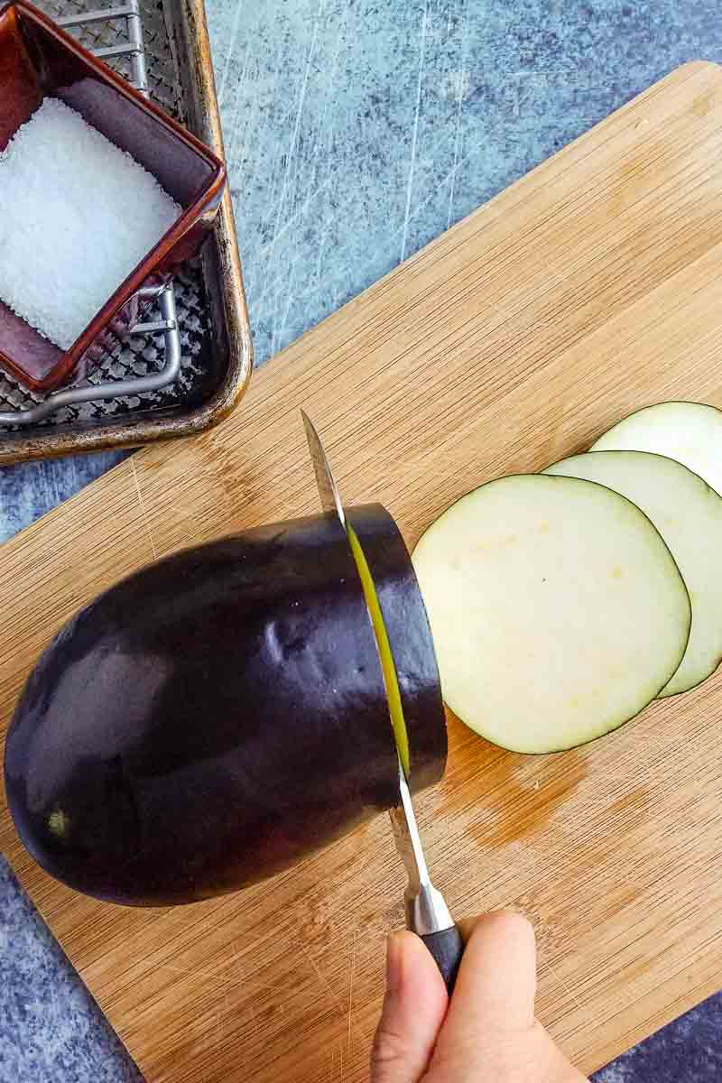 slicing eggplant on cutting board