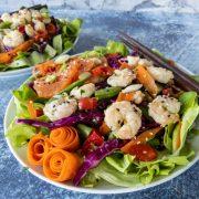 colorful sesame shrimp salad with chopsticks on concrete counter