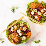 colorful salad with citrus fruit and shrimp in white bowls with chops sticks on marble counter