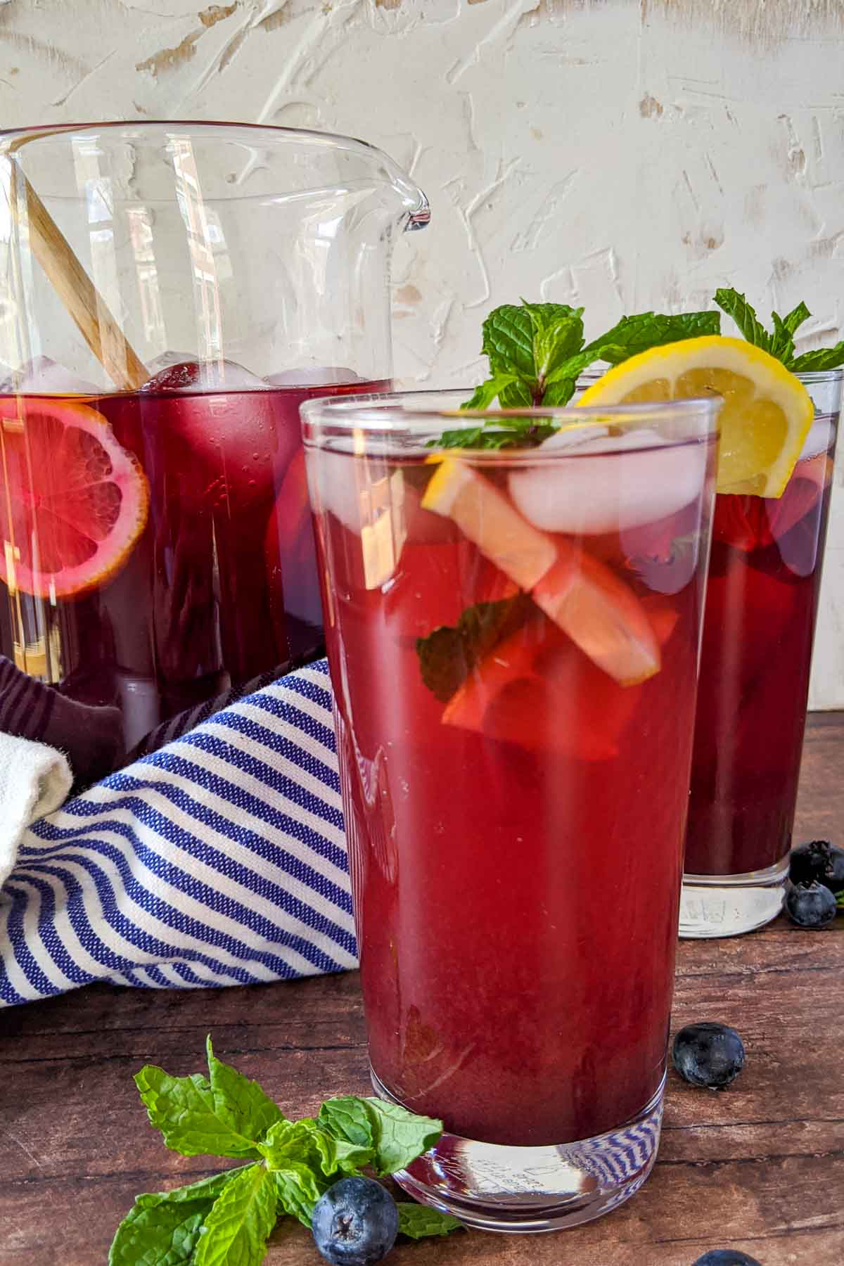 blueberry tea in glass with pitcher behind