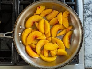 warming peaches in a pan for crisp