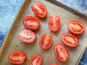 cut roma tomatoes on baking sheet