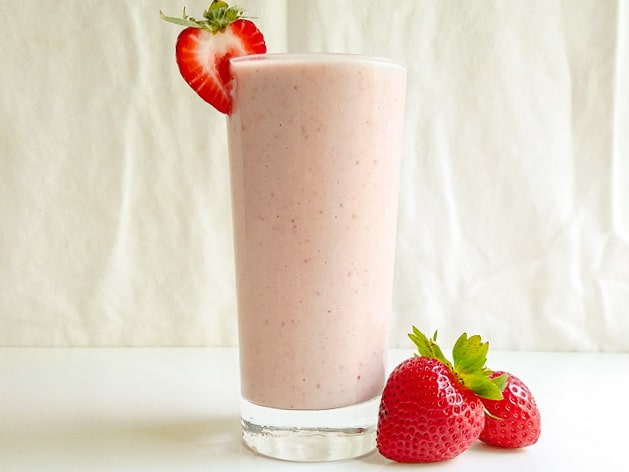 strawberry tahini milkshake in a glass with extra strawberries