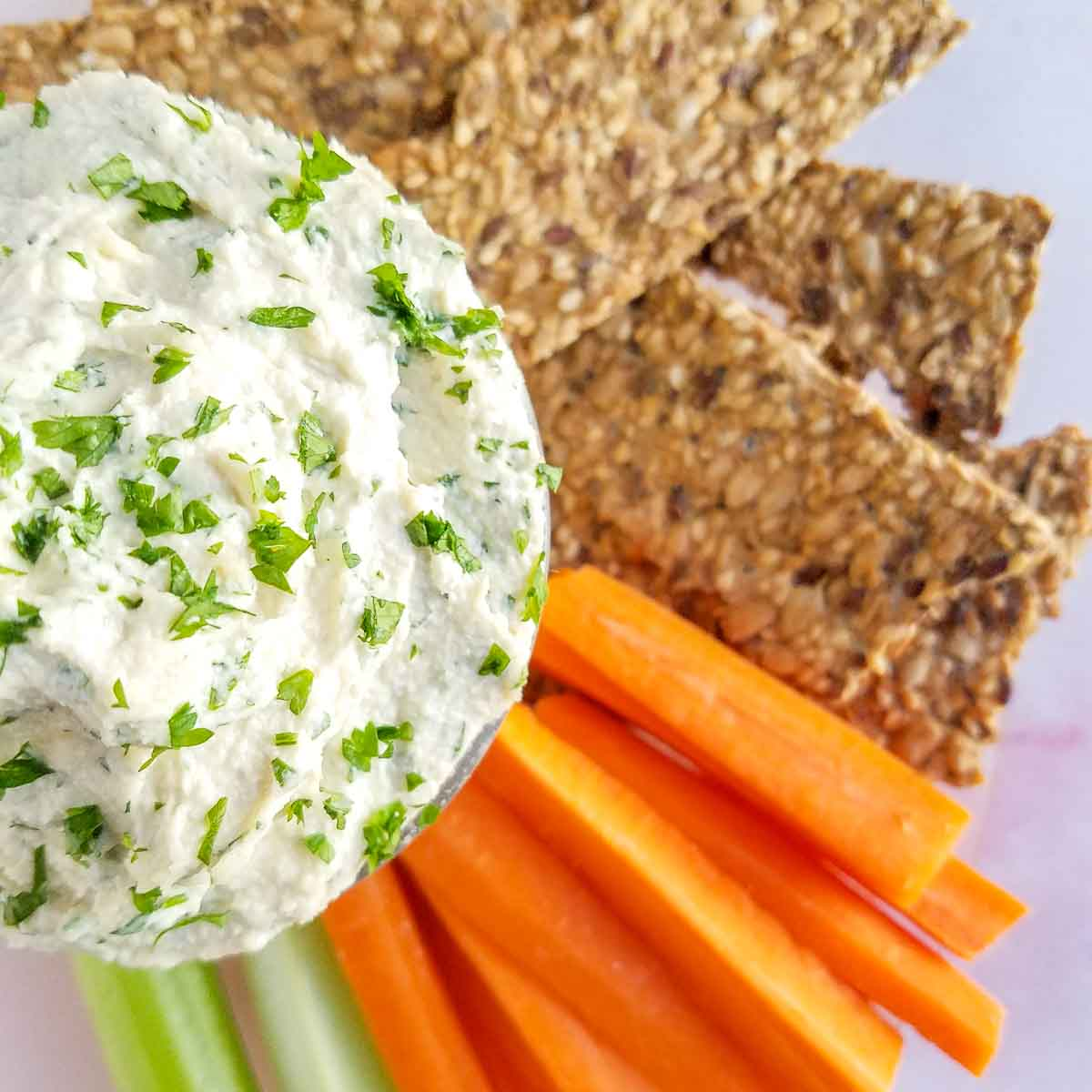 herb and garlic vegan cheese in a bowl with celery and carrots