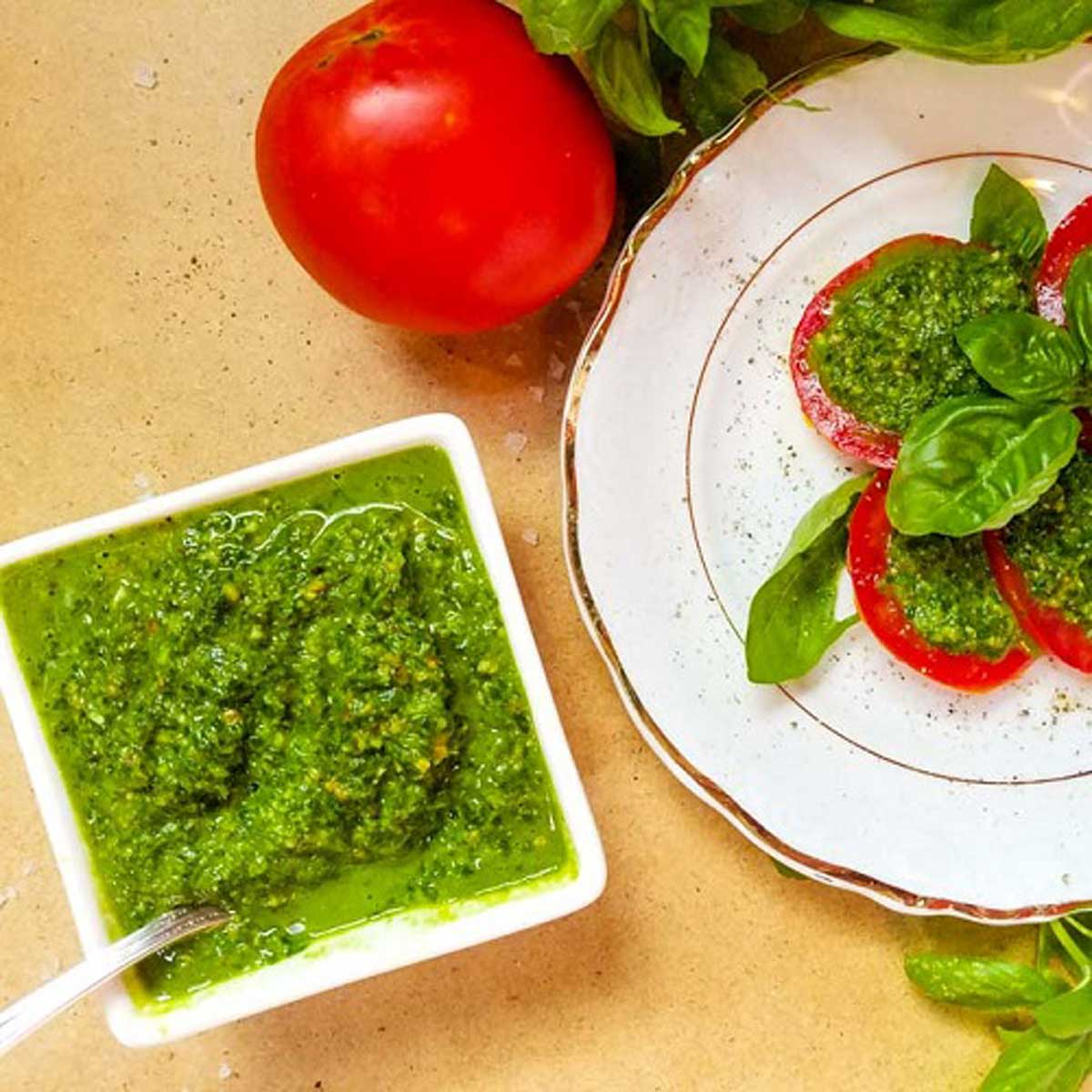 vegan pesto in a bowl with sliced tomatoes