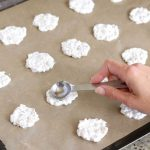 scooping frozen dog treats onto sheet pan