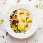chilled peach soup in white bowl with microgreens