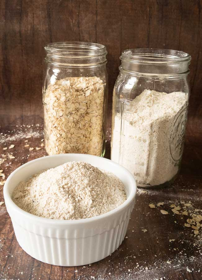 bowl of oat flour with jars of whole oat in back