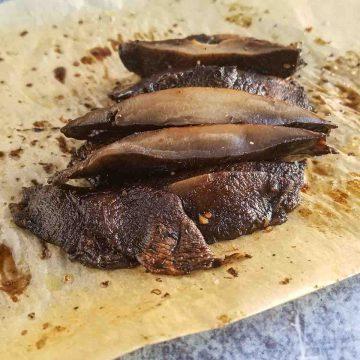 sliced portobello mushrooms on parchment paper