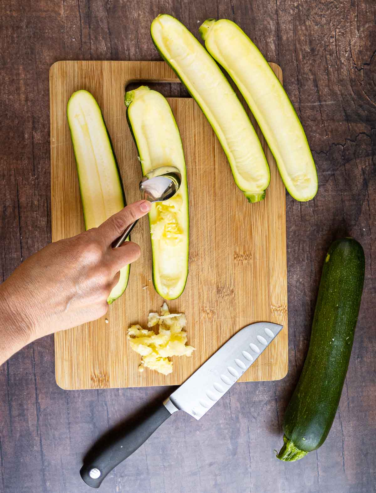 scrapping out the seeds of zucchini with a spoon