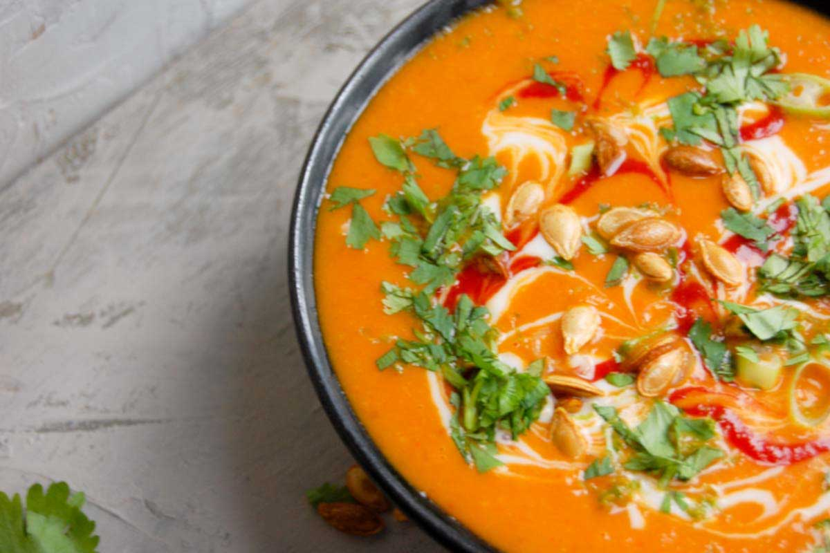 side view of spicy pumpkin soup with garnishes