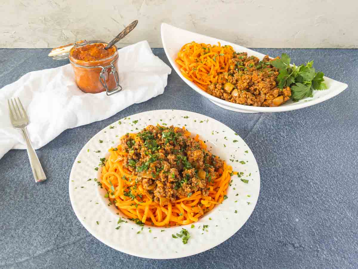 serving dish with harissa beef and individual boal of harissa beef over carrot noodles