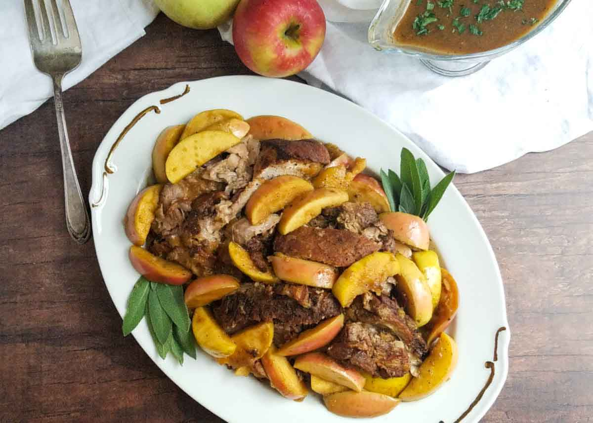 table with braised apple and onion pork roast on a platter