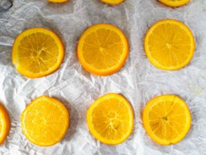 candied oranges cooling on parchment