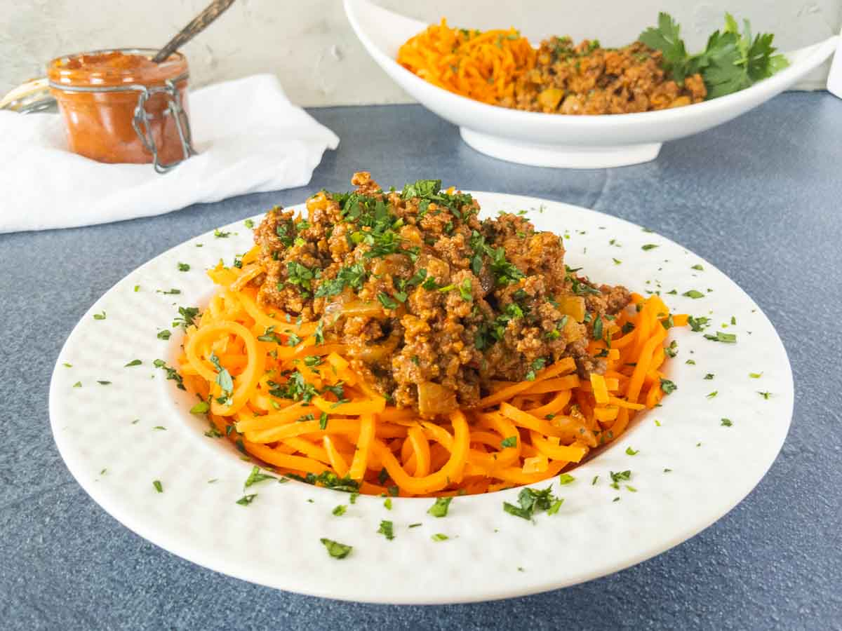 harissa beef and tomato over carrot noodles in a white bowl