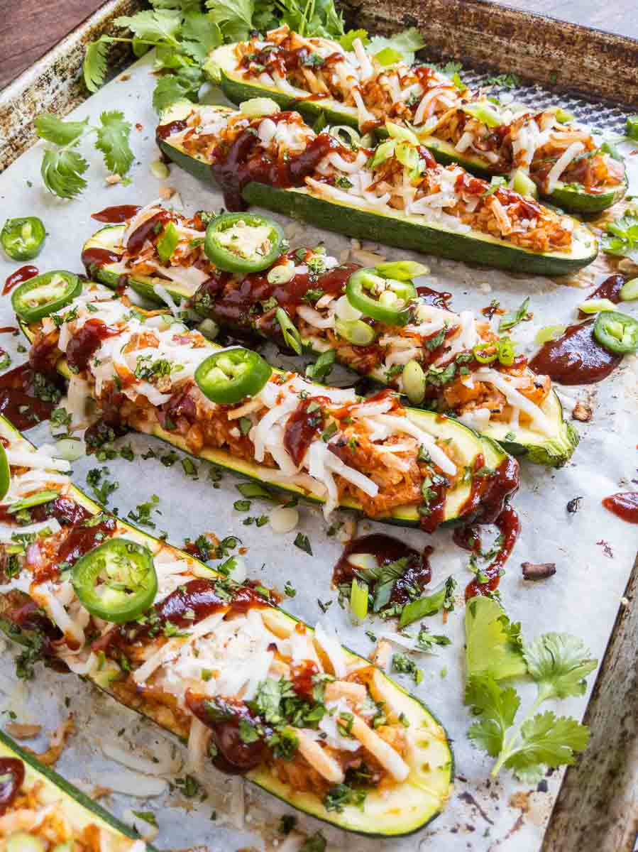 close up of chicken zucchini boats on parchment paper