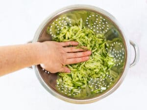 pressing water out of cucumber in colander