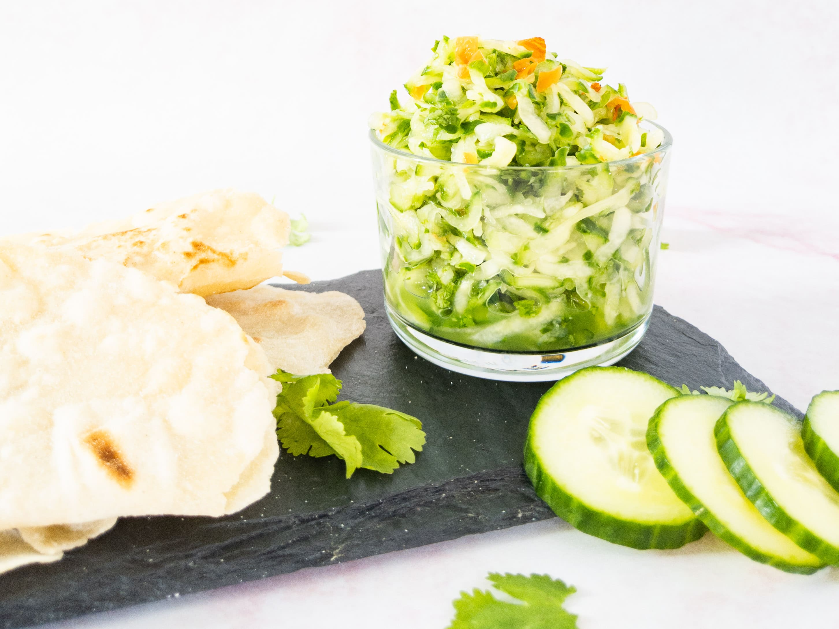 cucumber chutney in bowl with bread on side
