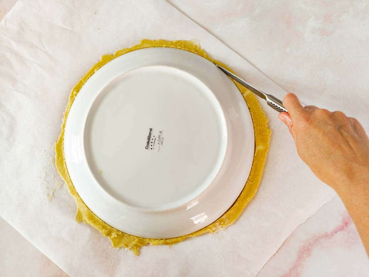 using a plate as template, cutting away excess dough
