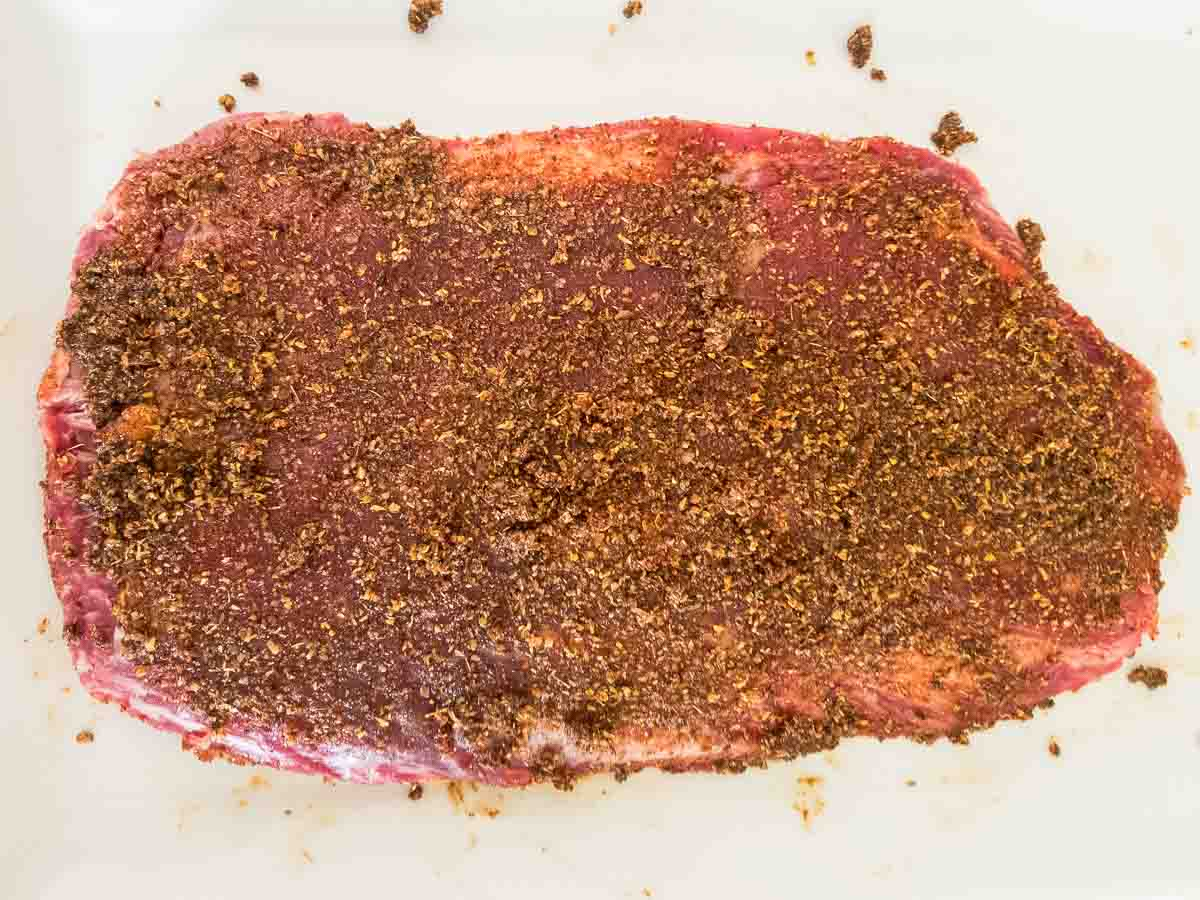 flank steak with seasoning before grilling