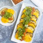 polenta cakes with eggplant and romesco on serving platter