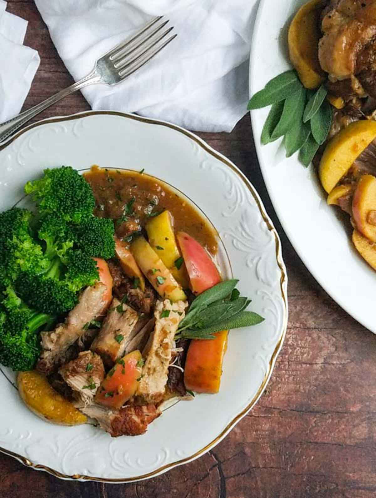 dinner plate with roast pork, apples and broccoli