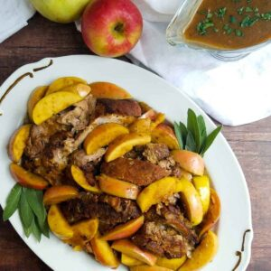 braised pork roast with sages and apples on a platter gravy boat to side
