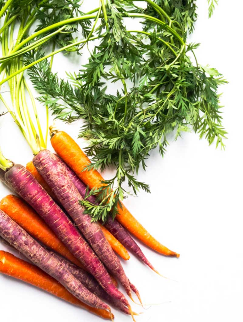 purple and orange carrots on white counter