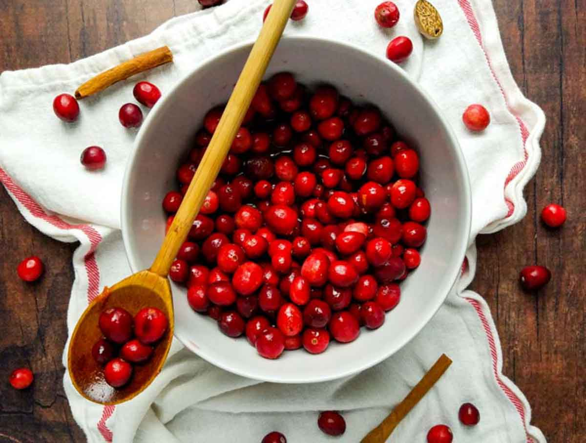 preparing cranberries in mixing bowl with wooden spoon