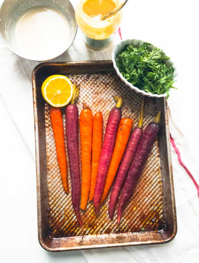 roasted purple carrots on a pan with tahini dressing