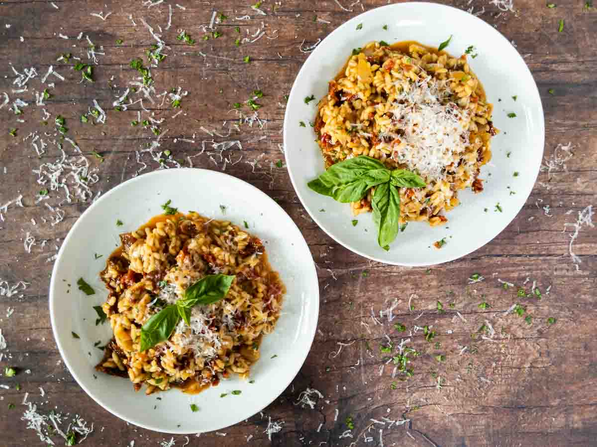 two bowls of tomato risotto on wooden counter