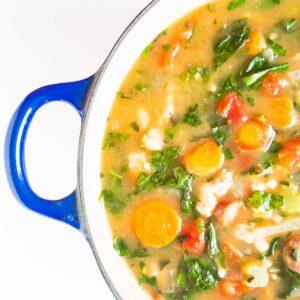 partial picture of turkey kale soup in a blue pot