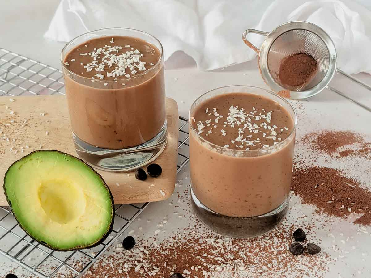 avocado and cocoa powder surrounding two glasses of chocolate spinach smoothies