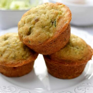 three zucchini muffins stacked on a plate