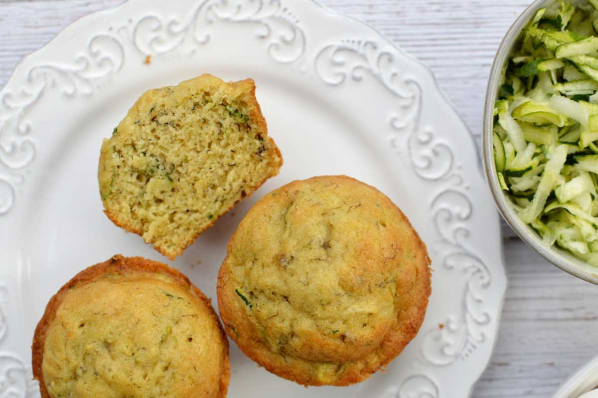 zucchini muffins on a plate and a bowl of grated zucchini