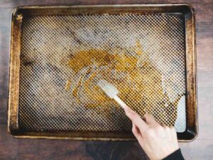mixing warm honey and olive oil on a sheet pan