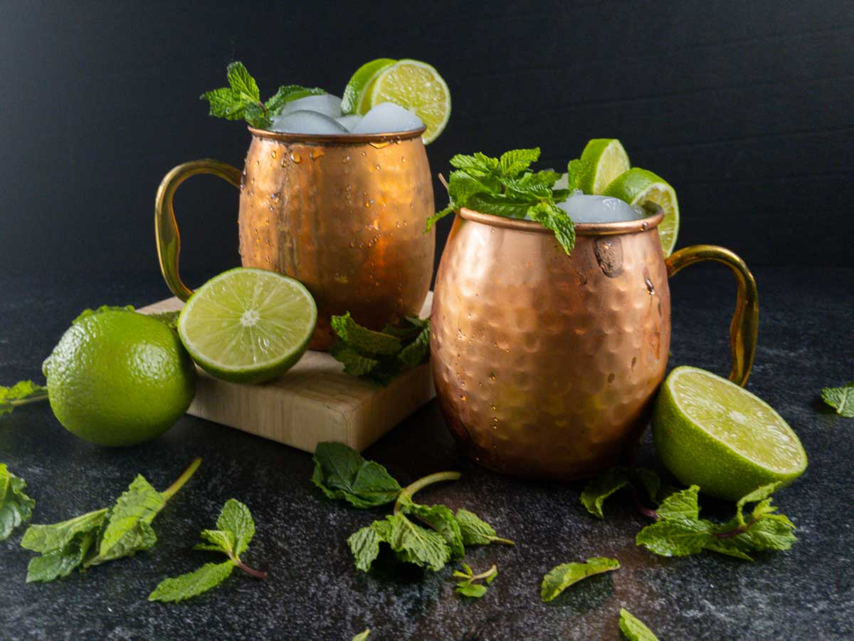 two mezcal mule cocktails in copper mugs with limes and mint