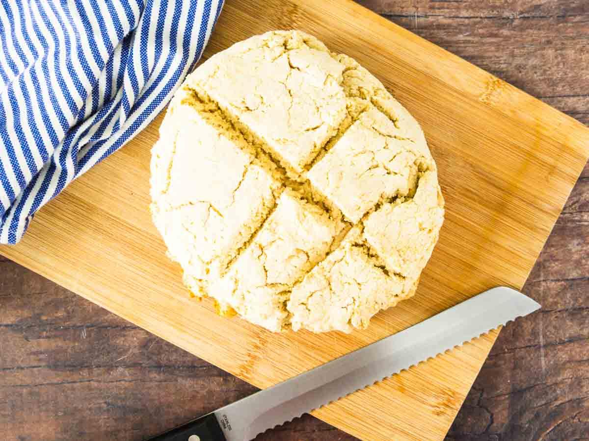 GF soda bread on cutting board with towel and bread knife