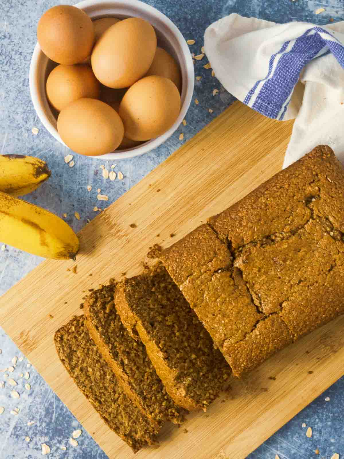 oat flour banana bread on cutting board with eggs and bananas
