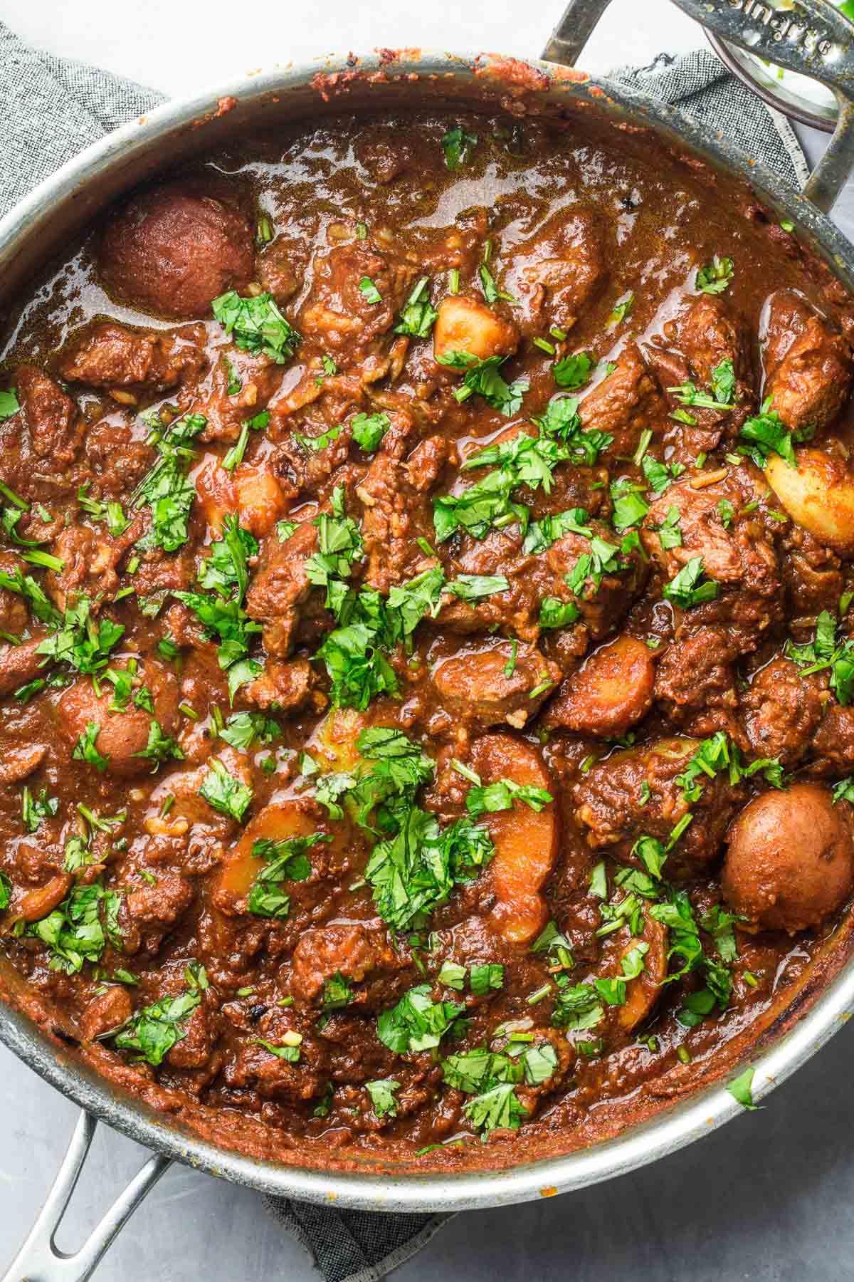 lamb curry in pan with cilantro garnish