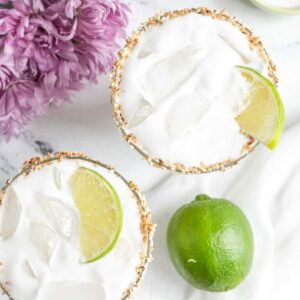 two glasses of coconut lime margaritas with lime garnish