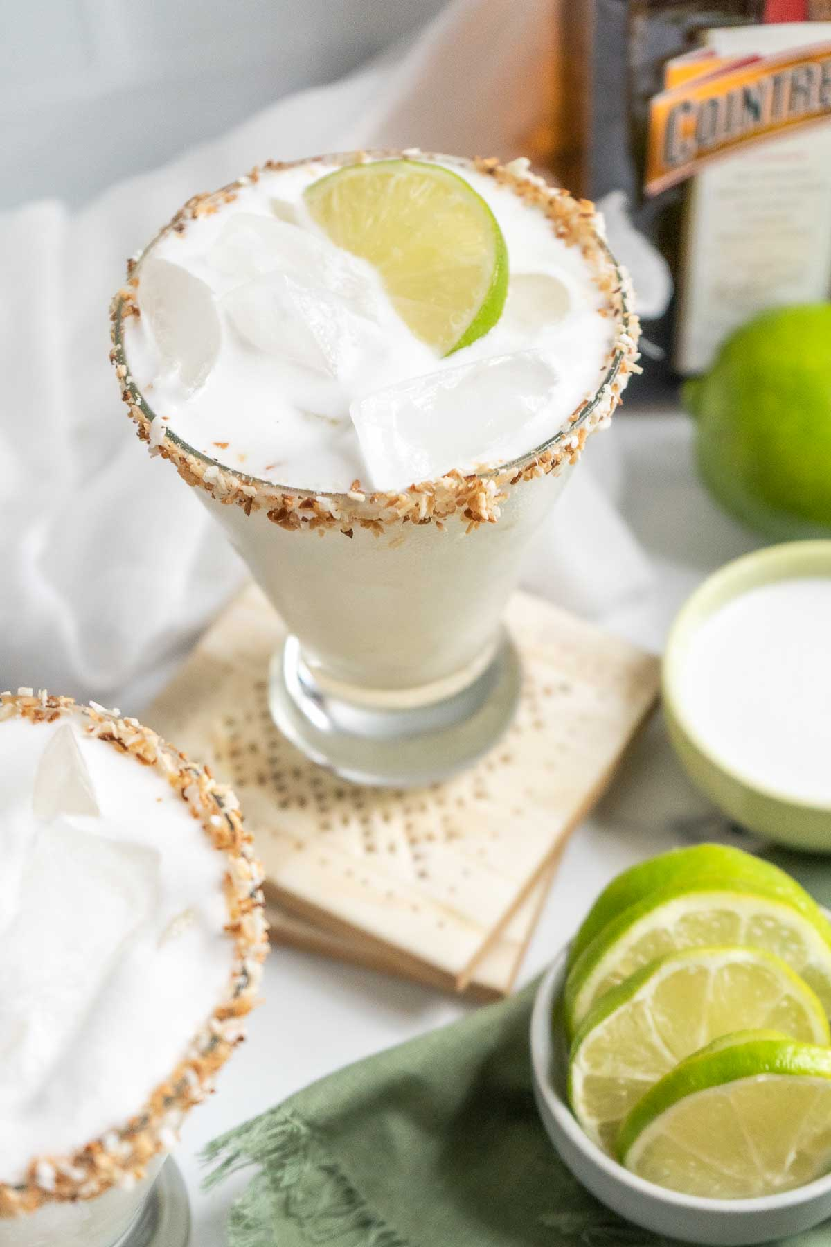 margarita in a glass with lime wedges scattered around